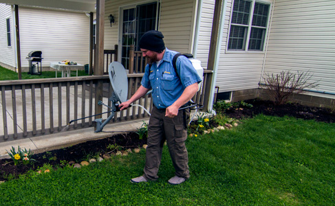 Licensed pest control technician, Jeremy Bannister completing a maintenance service on a residential home perimeter in Erie, PA to exterminate spiders, ants, centipedes.